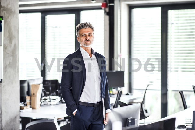 Portrait of confident mature businessman standing in office - HAPF02518
