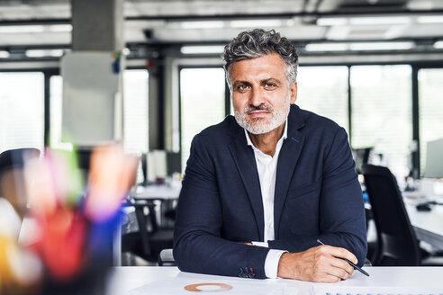 Portrait of confident mature businessman in office - HAPF02521