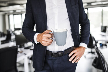 Close-up of businessman holding coffee mug in office - HAPF02533