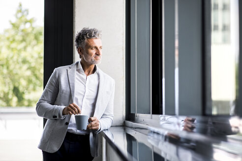 Smiling mature businessman with coffee mug looking out of window - HAPF02545