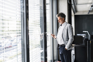 Mature businessman standing at the window in office holding cell phone - HAPF02557