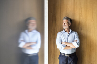Reflection of mature businessman standing at wooden wall - HAPF02569