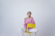 Portrait of laughing woman sitting on yellow chair - MOEF00427