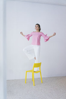 Happy young woman standing on yellow chair doing yoga exercise - MOEF00433