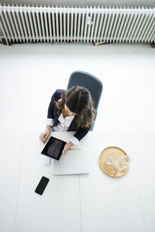 Businesswoman sitting at desk in the office working on tablet, top view - MOEF00442