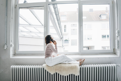 Young woman on the phone sitting on  sheepskin on heater in a loft looking out of window - MOEF00445