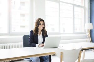 Portrait of laughing businesswoman sitting at desk in the office working on laptop - MOEF00448