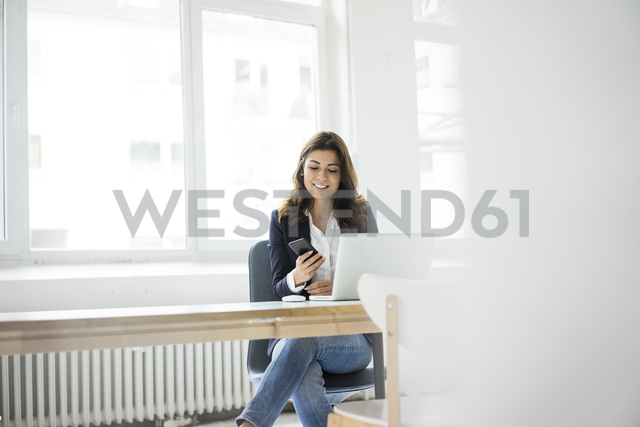 Businesswoman sitting at desk in the office working on laptop - MOEF00451
