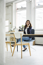 Portrait of laughing businesswoman on the phone sitting at desk in a loft - MOEF00454