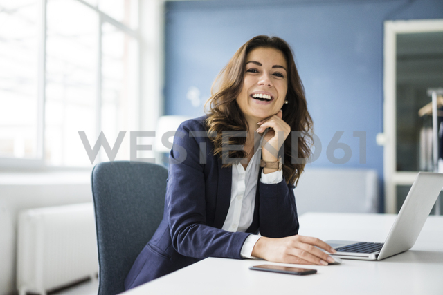 Portrait of laughing businesswoman sitting at desk in the office - MOEF00457