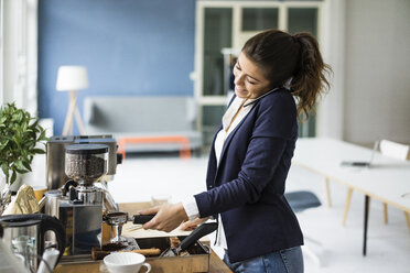 Smiling businesswoman on the phone preparing espresso with espresso machine in a loft - MOEF00466
