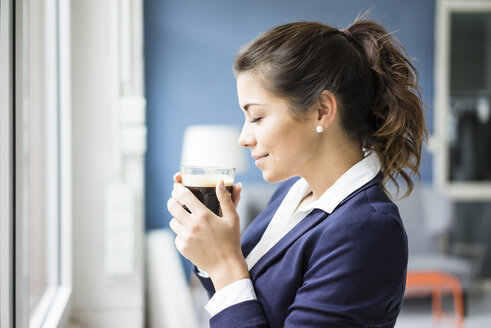 Smiling businesswoman enjoying glass of coffee - MOEF00469