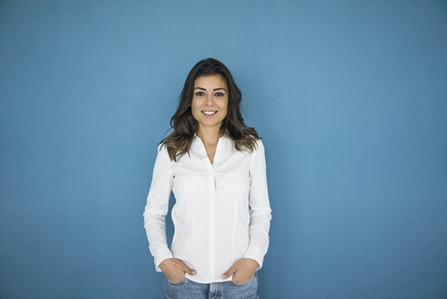 Portrait of smiling woman standing in front of blue wall - MOEF00472