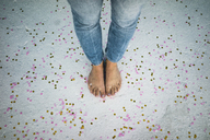 Feet of young woman standing in between confetti on the floor - MOEF00475