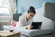 Portrait of laughing woman relaxing on couch with tablet - MOEF00478