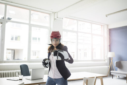 Portrait of businesswoman wearing ice hockey equipment in the office - MOEF00493