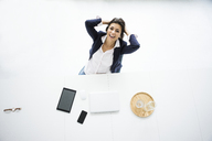 Portrait of laughing businesswoman having a break at desk in the office, top view - MOEF00499