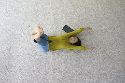 Laughing woman lying on carpet doing stretching exercises, top view - MOEF00502