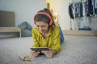 Smiling young woman lying on the floor using headphones and tablet - MOEF00508