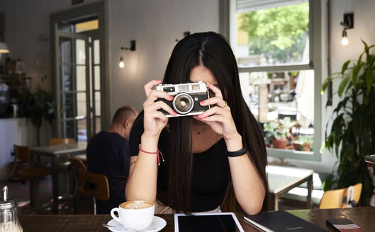 Brunette girl taking a picture with her film camera in a coffee shop - IGGF00299