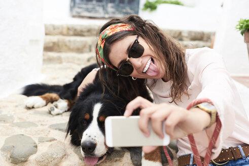 Brunette girl taking selfie, tired bernese mountain dog lying on the floor - IGGF00310