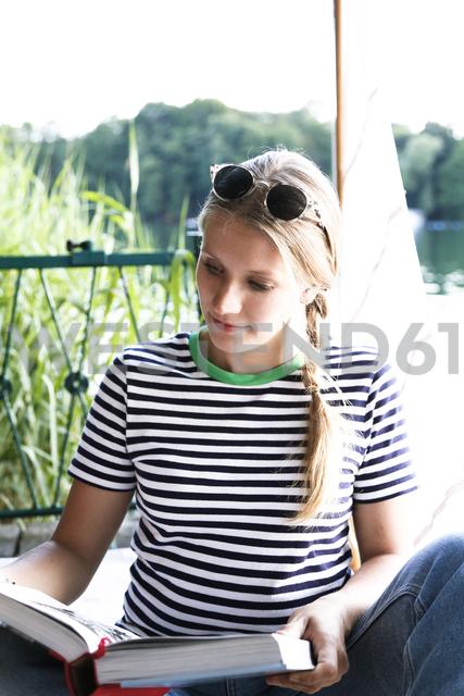 Young woman reading book at a lake next to sailing boat - FKF02792