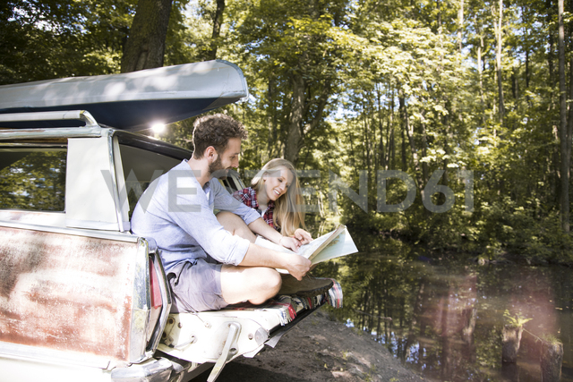 Smiling young couple with map and canoe in car at a brook - FKF02795