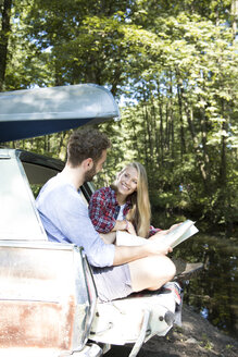 Smiling young couple with map and canoe in car at a brook - FKF02798
