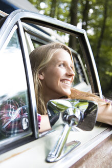 Happy young woman in car in forest - FKF02801