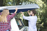 Smiling young couple taking canoe from car roof - FKF02804