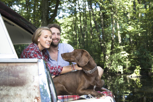 Smiling young couple with dog sitting in car at a brook in forest - FKF02807
