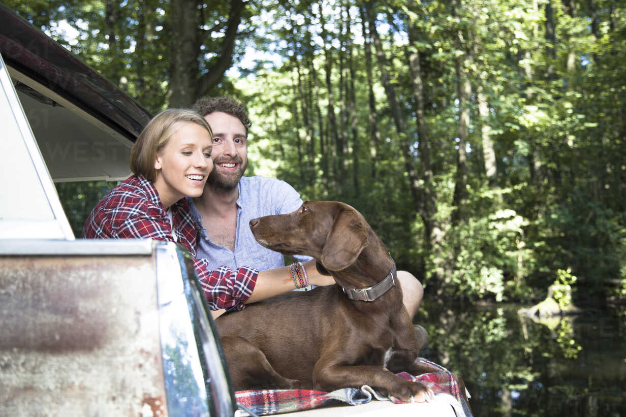 Smiling young couple with dog sitting in car at a brook in forest - FKF02807 - Florian Küttler/Westend61