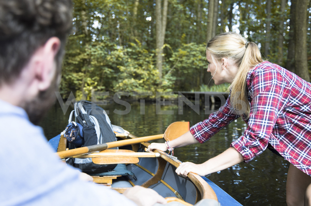 Young woman pulling canoe on a forest brook with man inside - FKF02810 - Florian Küttler/Westend61