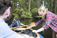 Young woman pulling canoe on a forest brook with man inside - FKF02810