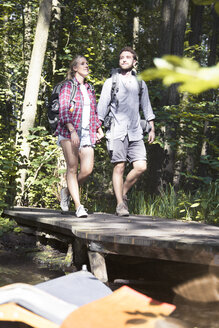 Young couple crossing a bridge in forest - FKF02813