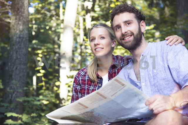 Smiling young couple with map in a forest - FKF02816