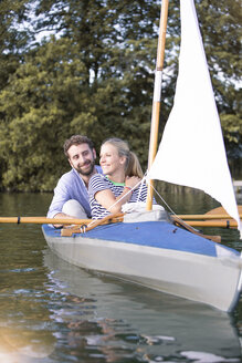 Happy young couple enjoying a trip in a canoe with sail - FKF02819
