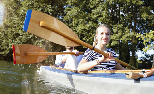 Young couple enjoying a trip in a canoe on a lake - FKF02825