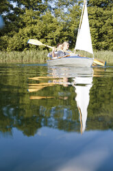 Young couple enjoying a trip in a canoe with sail on a lake - FKF02828