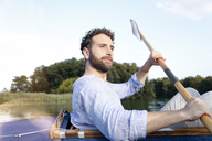 Young man enjoying a trip in a canoe on a lake - FKF02831