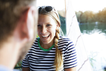 Young woman laughing at man at a lake next to sailing boat - FKF02837