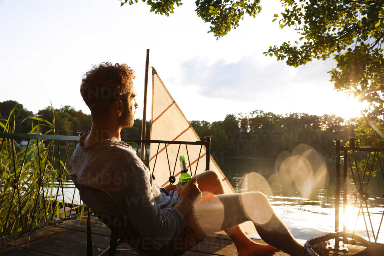 Young man with beer bottle sitting on a jetty next to sailing boat - FKF02846 - Florian Küttler/Westend61