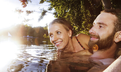 Happy young couple in a lake - FKF02849