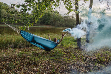 Young man lying in hammock with blue smoke torch - GUSF00281