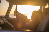 Spain, Tenerife, young woman lying in a van at sunset - SIPF01881