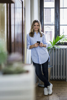 Portrait of smiling woman with cell phone at home - GIOF03597