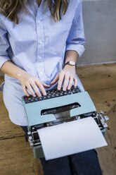Close-up of woman sitting on the floor using typewriter - GIOF03606