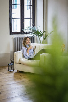 Woman relaxing on couch at home drinking coffee - GIOF03609