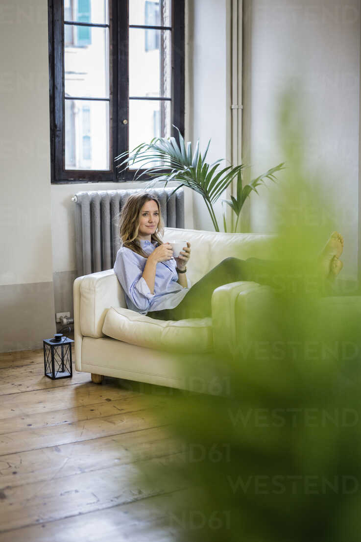 Woman relaxing on couch at home drinking coffee - GIOF03609 - Giorgio Fochesato/Westend61