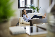 Smiling woman on couch at home on the phone - GIOF03612